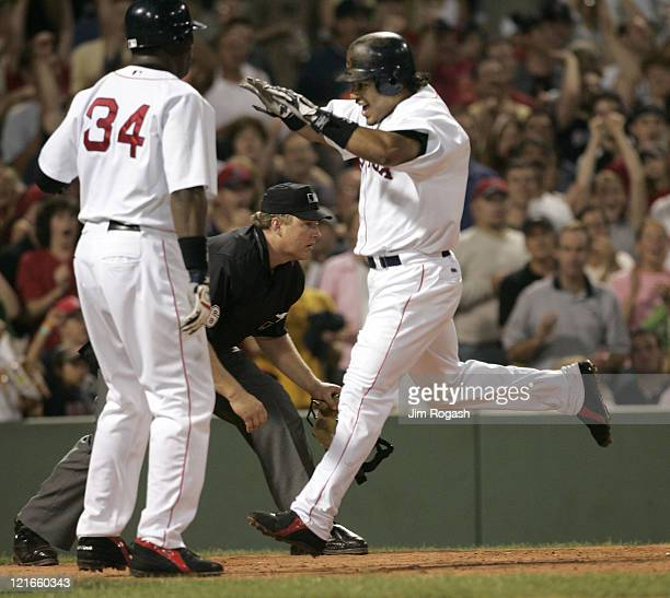 Boston Red Sox base runner Manny Ramirez right reacts as he scores a run against the Oakland Athletics at Fenway Park in Boston July 8 2004 The Red...