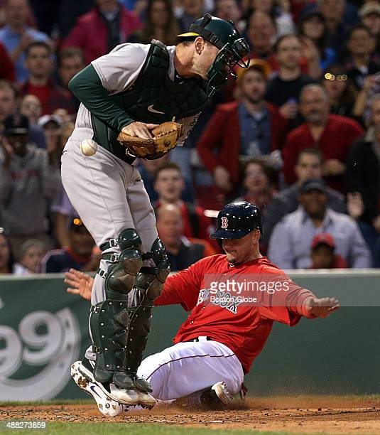 Boston Red Sox catcher AJ Pierzynski signals safe as he slides home safely scoring the second run of the game on a RBI double by Boston Red Sox...