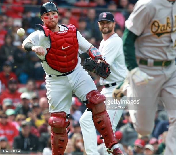 Boston Red Sox catcher Christian Vazquez comes out from behind the plate to throw out Oakland's Stephen Piscotty in the top of the seventh inning...