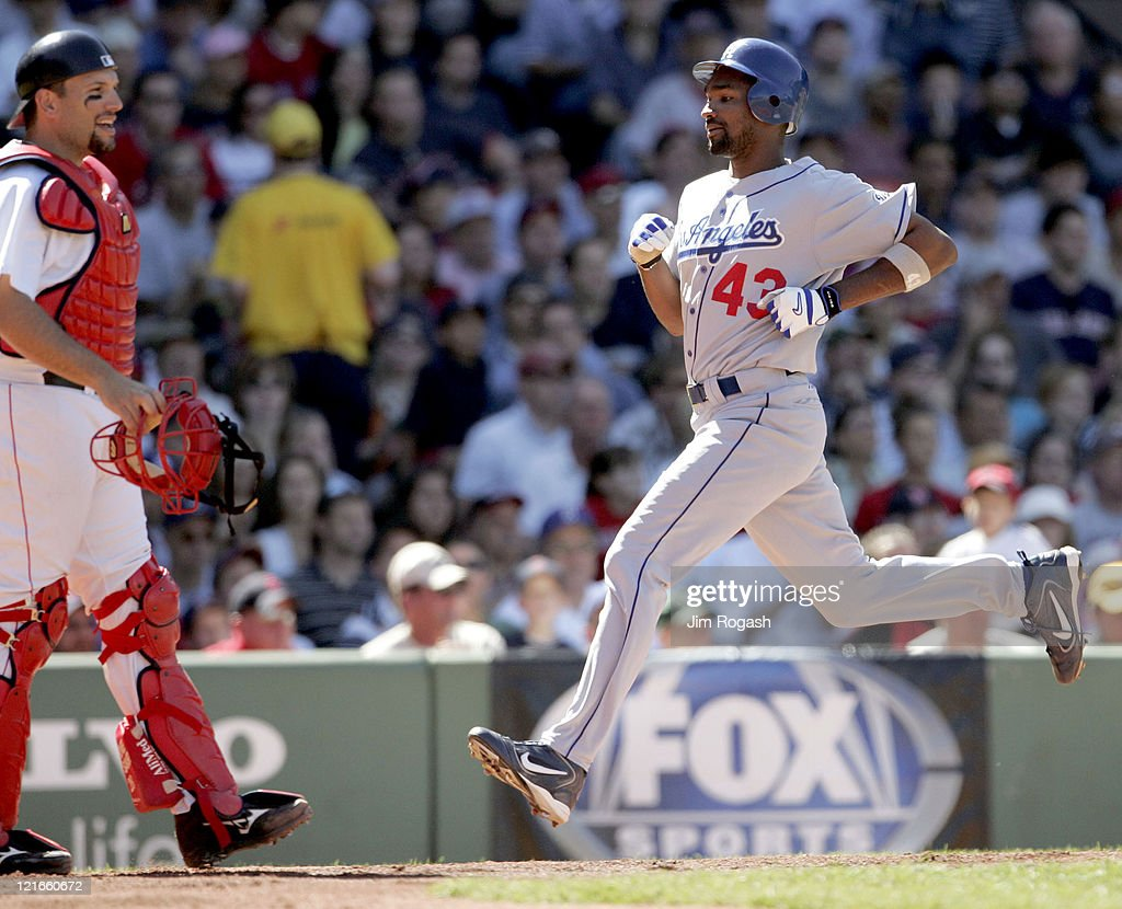 Boston Red Sox catcher Doug Mirabelli, left, watches the actions as Los Angeles Dodgers base runner Juan Encarnacion scores at Fenway Park in Boston, Massachusetts on June 12, 2004.