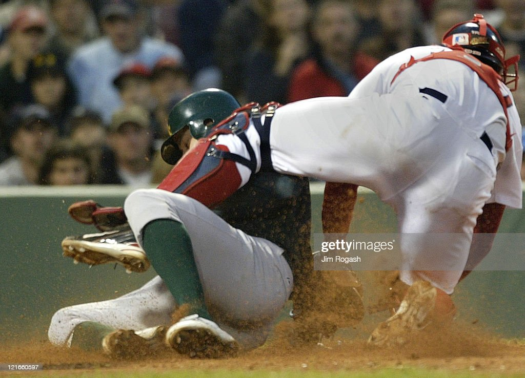 Boston Red Sox catcher Jason Varitek is late with the tag as Oakland Athletics' Bobby Crosby slides safely home, Thursday, May 27, 2004. The Red Sox lost 15-2 at Fenway Park in Boston, Massachusetts.
