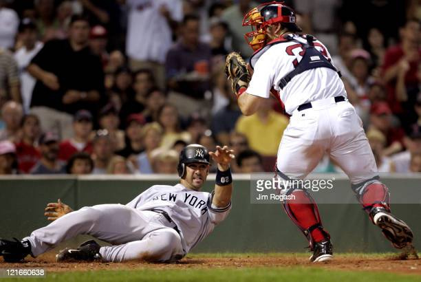 Boston Red Sox catcher Jason Varitek right is late with the tag as New York Yankees' Jorge Posada scores at Fenway Park in Boston Massachuesetts on...