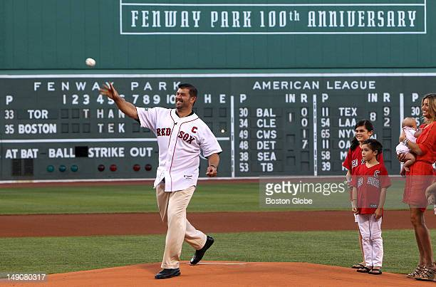 Boston Red Sox catcher Jason Varitek throws out the ceremonial first pitch accompanied by his wife and daughters during a pregame ceremony honoring...