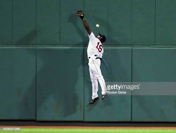 Boston Red Sox center fielder Jackie Bradley Jr casts shadows as he leaps but can't make the play on a top of the fourth inning triple off the wall...