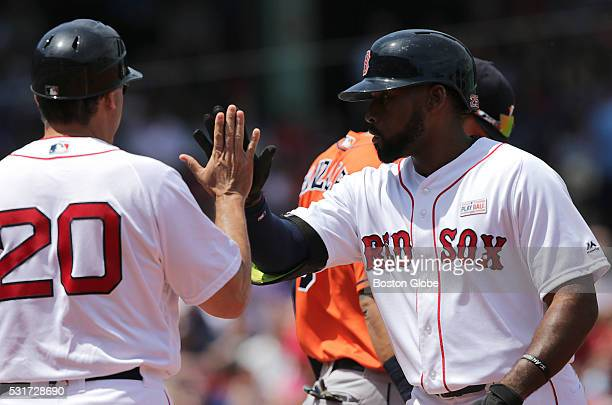 Boston Red Sox center fielder Jackie Bradley Jr gets a high five from Boston Red Sox first base coach Ruben Amaro Jr left after his single in the...