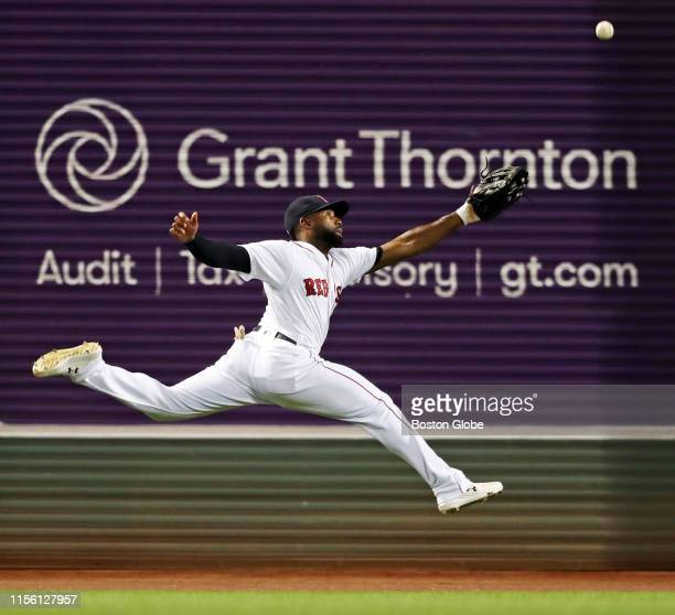 Boston Red Sox center fielder Jackie Bradley Jr leaps but can't make the play on a top of the ninth inning leadoff triple hit by Toronto left fielder...