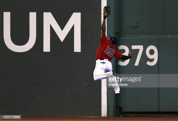 Boston Red Sox center fielder Jackie Bradley Jr. Leaps to make an over the shoulder catch of a deep drive to the center field wall by Tampa Bay Rays...