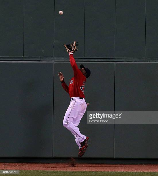 Boston Red Sox center fielder Jackie Bradley Jr makes a defensive catch up against the Boston Centerfield wall and then throws to first base in time...