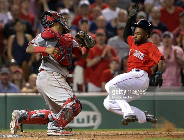 Boston Red Sox center fielder Jackie Bradley Jr slides into home plate evading the tag of Los Angeles Angels catcher Martin Maldonado in the eighth...
