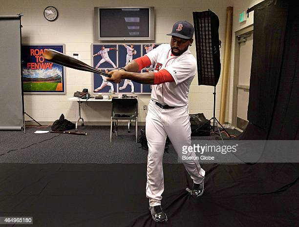 Boston Red Sox center fielder Jackie Bradley Jr takes a swing for a photographer during spring training picture day
