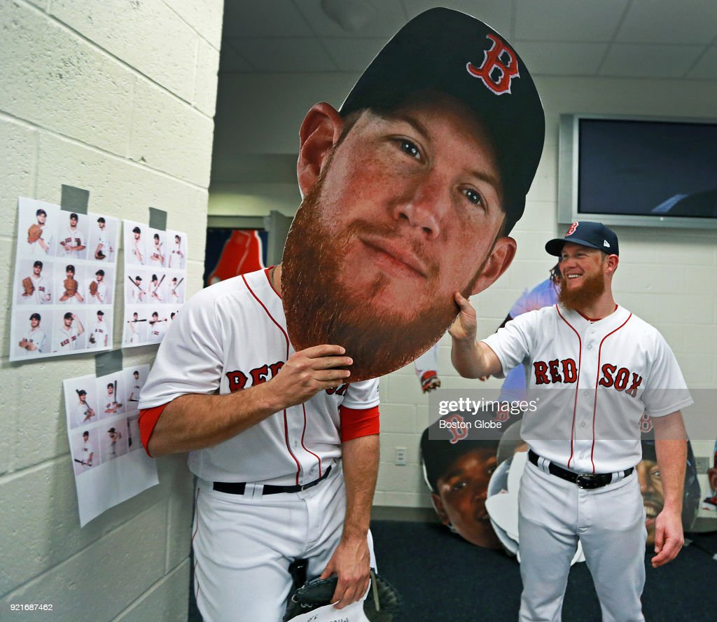 Boston Red Sox closer Craig Kimbrel, right, laughs while teammate Mitch Moreland holds up an oversized cutout of Kimbrel's face as players posed for promotional photos during spring training at the Player Development Complex at Jet Blue Park in Fort Myers, FL on Feb. 20, 2018.