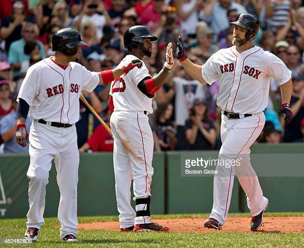 Boston Red Sox David Ross high fives his teammates Jackie Bradley Jr and Shane Victorino after hitting a tworun home run against the Kansas City...