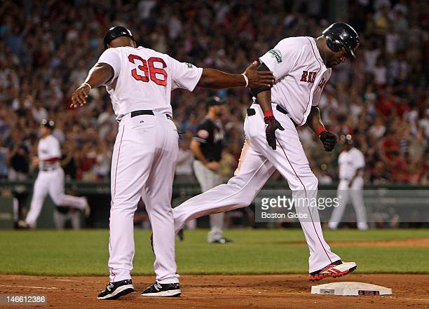 Boston Red Sox designated hitter David Ortiz is congratulated by Boston Red Sox first base coach Alex Ochoa as he rounds first on his way to touching...