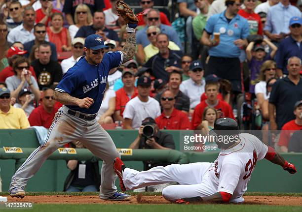 Boston Red Sox designated hitter David Ortiz slides safely into third base on a double by Boston Red Sox right fielder Cody Ross in the fourth inning...