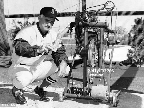Boston Red Sox first base coach Bobby Doerr examines a batting practice machine during Red Sox Spring Training in Winter Haven FL on Feb 27 1967