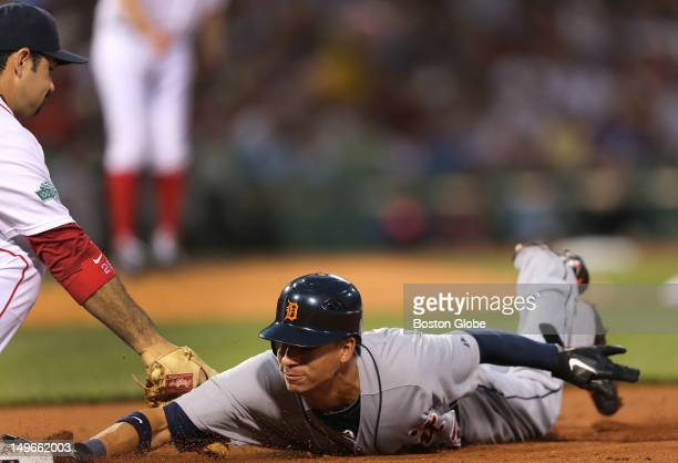 Boston Red Sox first baseman Adrian Gonzalez slaps the tag on Detroit Tigers left fielder Quintin Berry who was picked off first base in the fourth...