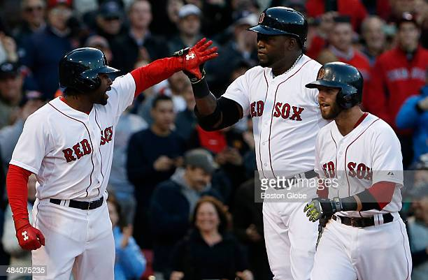 Boston Red Sox Jackie Bradley Jr left celebrates Red Sox teammate David Ortiz's three run home run at the plate with Red Sox Dustin Pedroia right...