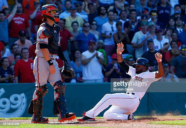 Boston Red Sox Jackie Bradley Jr right slides safely into home in front of Baltimore Orioles catcher Caleb Joseph during the seventh inning at Fenway...