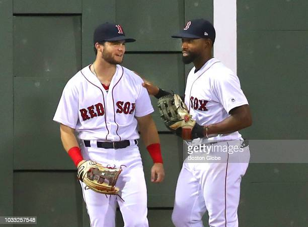 Boston Red Sox left fielder Andrew Benintendi left gets a pat from centerfielder Jackie Bradley Jr after they came close to a collision as Benintendi...