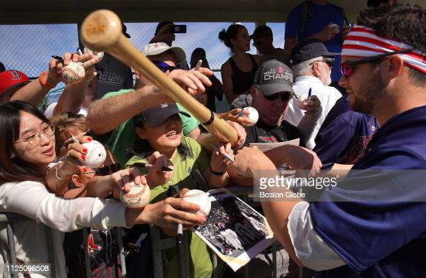 Boston Red Sox left fielder Andrew Benintendi signs autographs for fans following an informal workout for position players during spring training at...