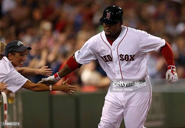 Boston Red Sox left fielder Carl Crawford gets a hand from the fans after his solo homer in the seventh inning as the Boston Red Sox took on the...