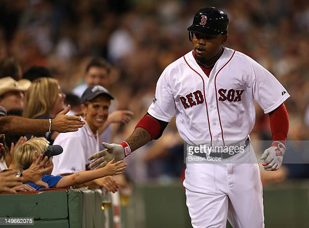 Boston Red Sox left fielder Carl Crawford gets a hand from the fans after his solo homer in the seventh inning the Boston Red Sox took on the Detroit...