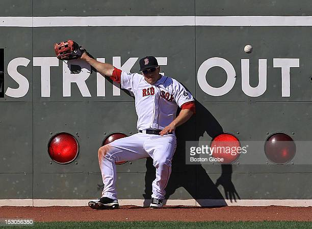 Boston Red Sox left fielder Daniel Nava leaps but is unable to make the catch of a double off the wall by Baltimore Orioles third baseman Manny...
