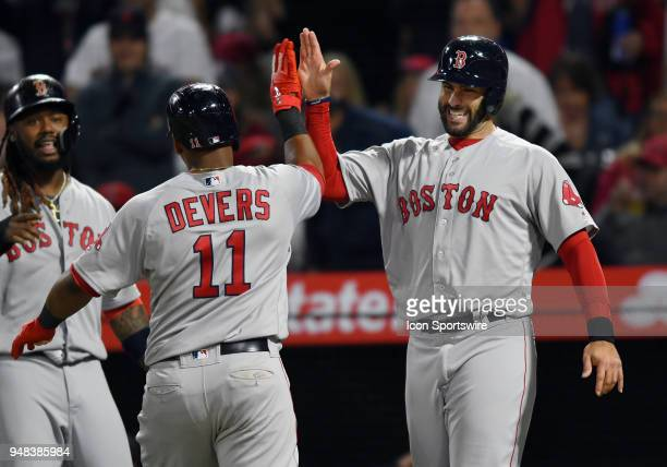 Boston Red Sox left fielder JD Martinez high fives third baseman Rafael Devers at home plate after Devers hit a grand slam in the third inning of a...