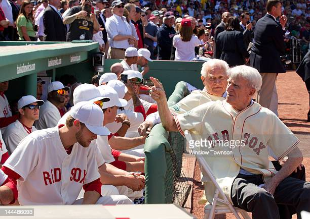 Boston Red Sox legends Johnny Pesky front and Bobby Doerr sit outside the Red Sox dugout before the game between the Boston Red Sox and the New York...