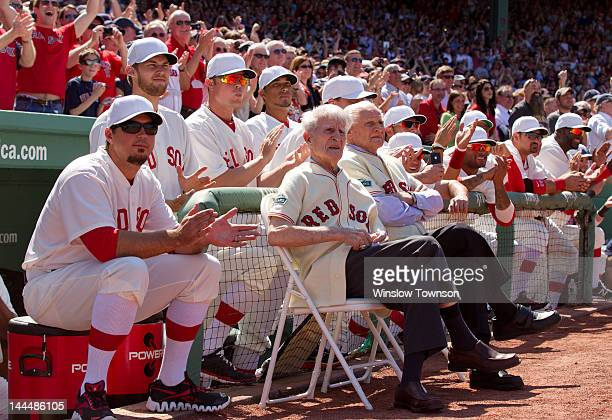 Boston Red Sox legends Johnny Pesky left and Bobby Doerr sit in chairs in front of the Red Sox dugout with current Red Sox players before the game...