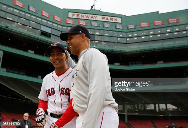 Boston Red Sox manager Alex Cora and Julio Lugo chat before the start of the Red Sox alumni game at Fenway Park in Boston on May 27 2018