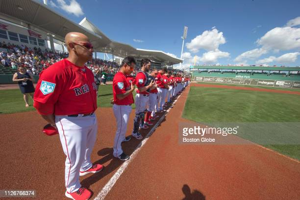 Boston Red Sox manager Alex Cora and the team stand at attention during a moment of silence for late Boston Globe baseball writer Nick Cafardo before...