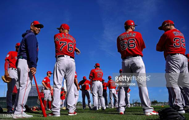 Boston Red Sox manager Alex Cora in blue at left stands with players during a spring training pitchers and catchers workout at JetBlue Park in Fort...