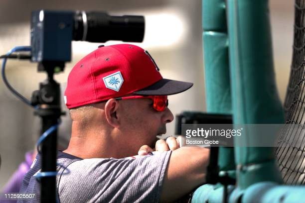 Boston Red Sox manager Alex Cora is framed by a high speed camera as he watches a live batting practice session during a spring training workout at...