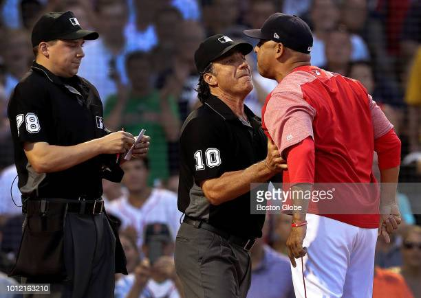 Boston Red Sox manager Alex Cora is restrained by umpire Phil Cuzzi as he argues with home plate umpire Adam Hamari during the first inning Cora was...