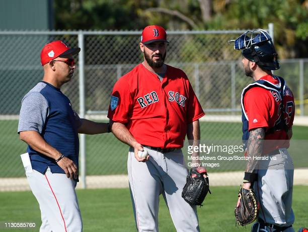 Boston Red Sox manager Alex Cora left and catcher Blake Swihart talk with pitcher Bradon Workman during a spring training workout in Fort Myers...
