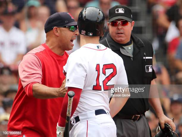 Boston Red Sox manager Alex Cora pulls player Brock Holt away from home plate umpire Doug Eddings after Holt was called out on strikes during the...