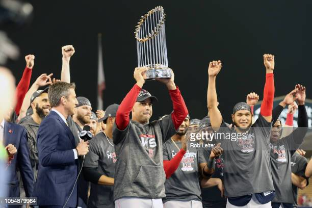 Boston Red Sox manager Alex Cora raises the World Series trophy after the Boston Red Sox defeat the Los Angeles Dodgers during Game 5 of the 2018...