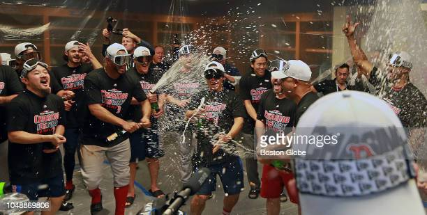 Boston Red Sox manager Alex Cora right with hat and champagne in hand gets the party started by popping the first cork in the clubhouse following...