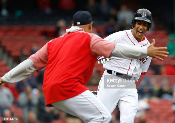 Boston Red Sox manager Alex Cora runs out to congratulate Julio Lugo as he runs up the first baseline on a home run during the Red Sox alumni game at...