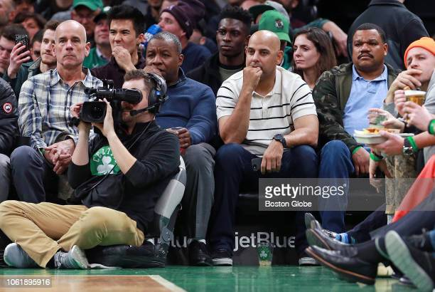 Boston Red Sox manager Alex Cora second from right takes in the game from front row courtside seats joined by team clubhouse workers from left Tommy...