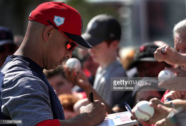 Boston Red Sox manager Alex Cora signs autographs for fans during a spring training pitchers and catchers workout at JetBlue Park in Fort Myers FL on...