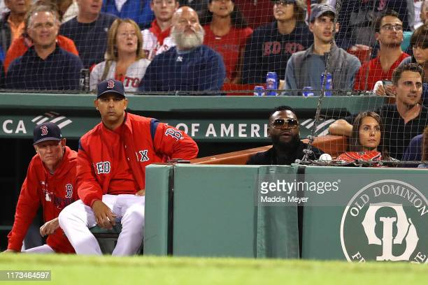 Boston Red Sox manager Alex Cora sits in the dugout next to David Ortiz and his wife Tiffany during the first inning of the game between the Boston...