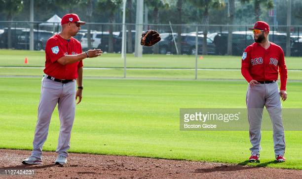 Boston Red Sox manager Alex Cora tosses a glove to second baseman Dustin Pedroia during spring training at JetBlue Park in Fort Myers FL on Feb 18...