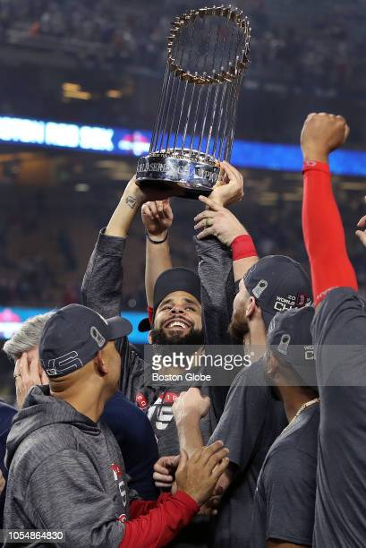 Boston Red Sox manager Alex Cora turns and watches as starting pitcher David Price hoists the trophy as the Red Sox celebrate their World Series...