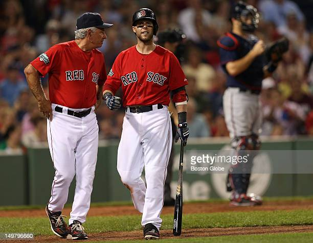 Boston Red Sox manager Bobby Valentine walks Boston Red Sox second baseman Dustin Pedroia back to the dugout after Pedroia argued a third called...