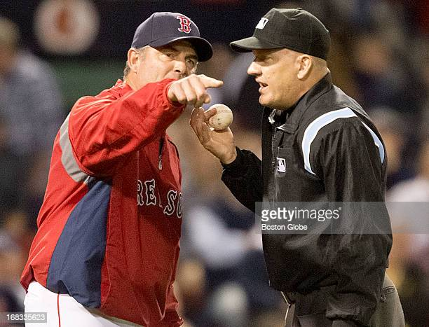 Boston Red Sox manager John Farrell argues with home plate umpire Jeff Nelson after Minnesota Twins player Ryan Doumit ran out of the baseline...