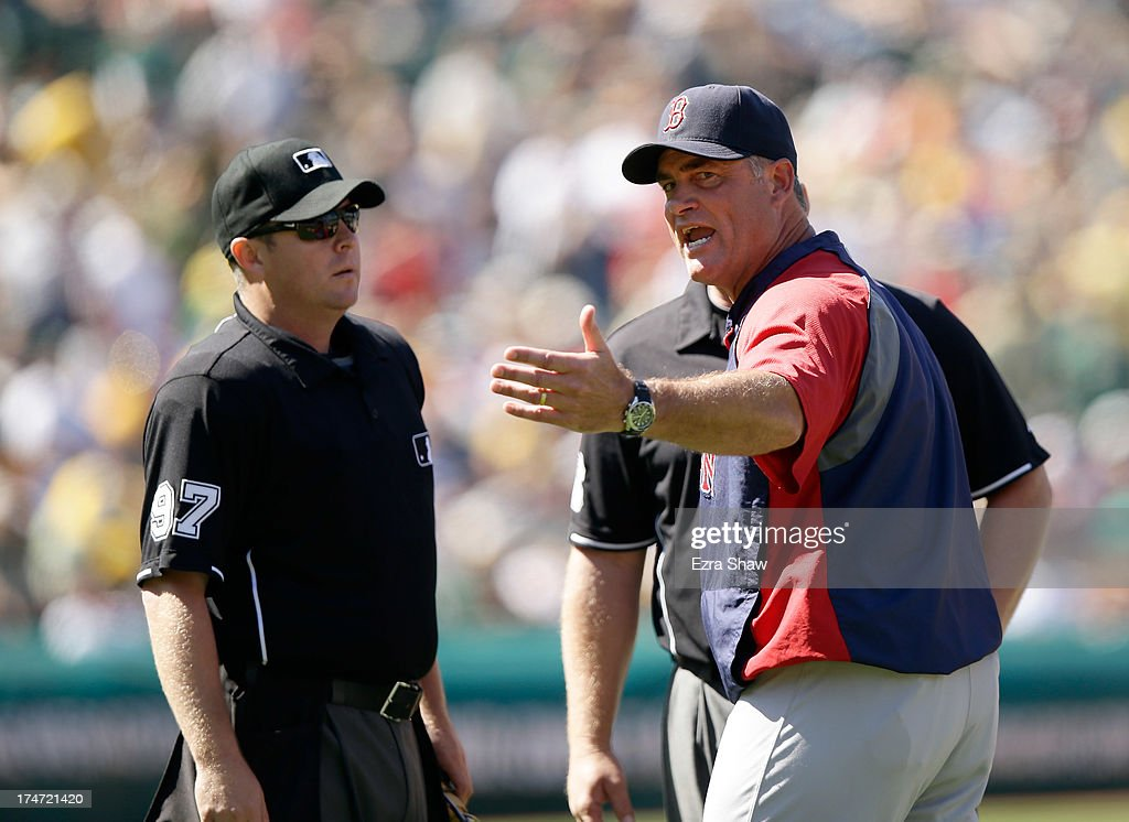 Boston Red Sox manager John Farrell argues with umpires Todd Tichenor (left) and Bill Miller after Gomes struck out in the ninth inning of their game against the Oakland Athletics at O.co Coliseum on July 14, 2013 in Oakland, California.
