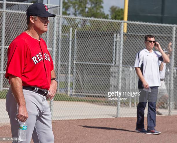 Boston Red Sox manager John Farrell left watches practice as general manager Ben Cherington talks on the phone Day two of spring training at the Red...