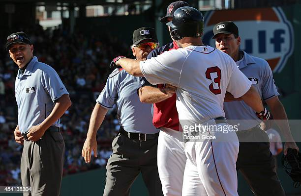 Boston Red Sox manager John Farrell restrains an angry David Ross from confronting first base umpire Vic Carapazza at far left after Ross felt he had...
